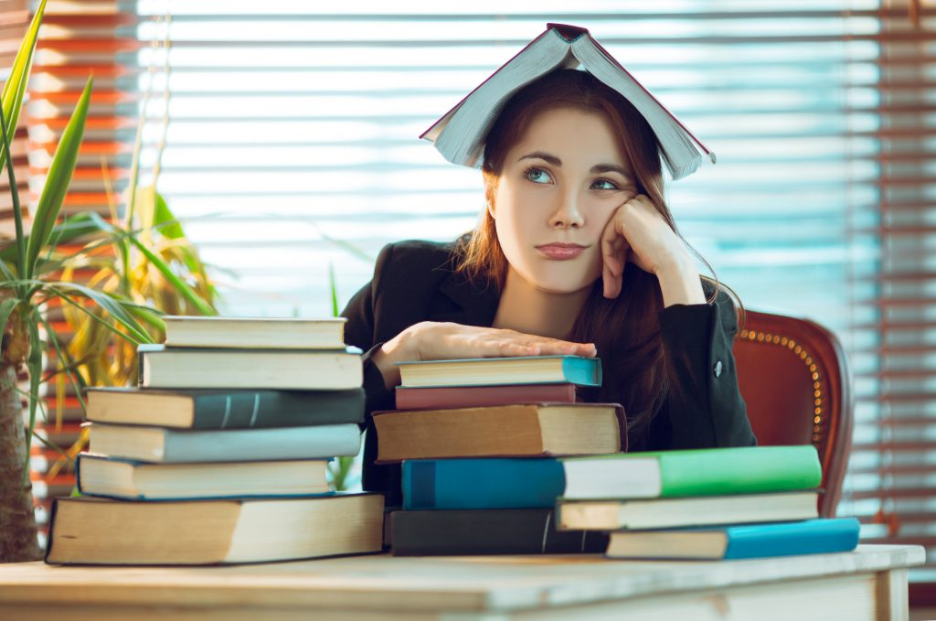 Portrait of beautiful student girl sitting among books with a book on her head